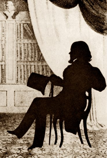 A silhouette of August Edouart with his duplicate albums.
