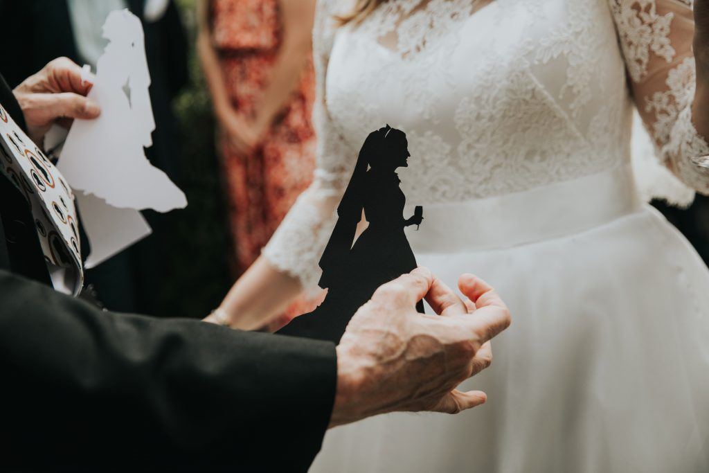 Silhouette of a bride held up against her dress