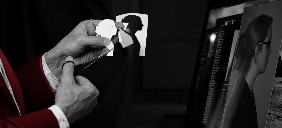 Hands holding paper silhouette and scissors in fron of a computer screen