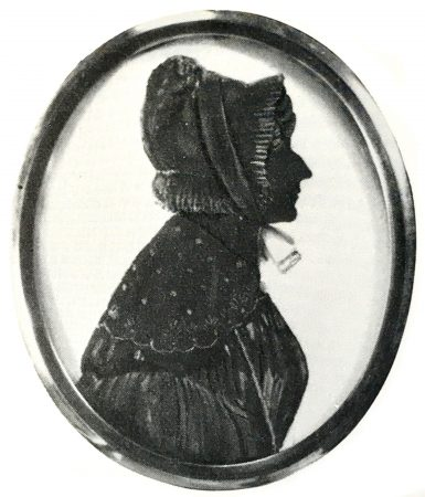 Silhouette of a woman with a bonnet and shawl, painted in some detail