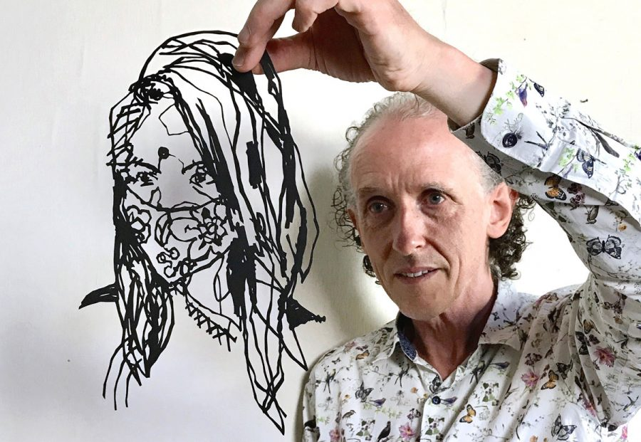 Charles holding an unmounted paper cutting up to the camera